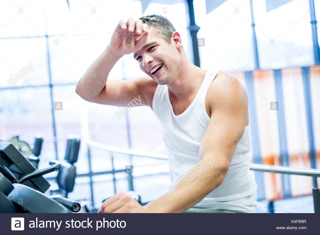 PROPERTY RELEASED. MODEL RELEASED. Young man sweating while exercising in gym, smiling. - Stock Image