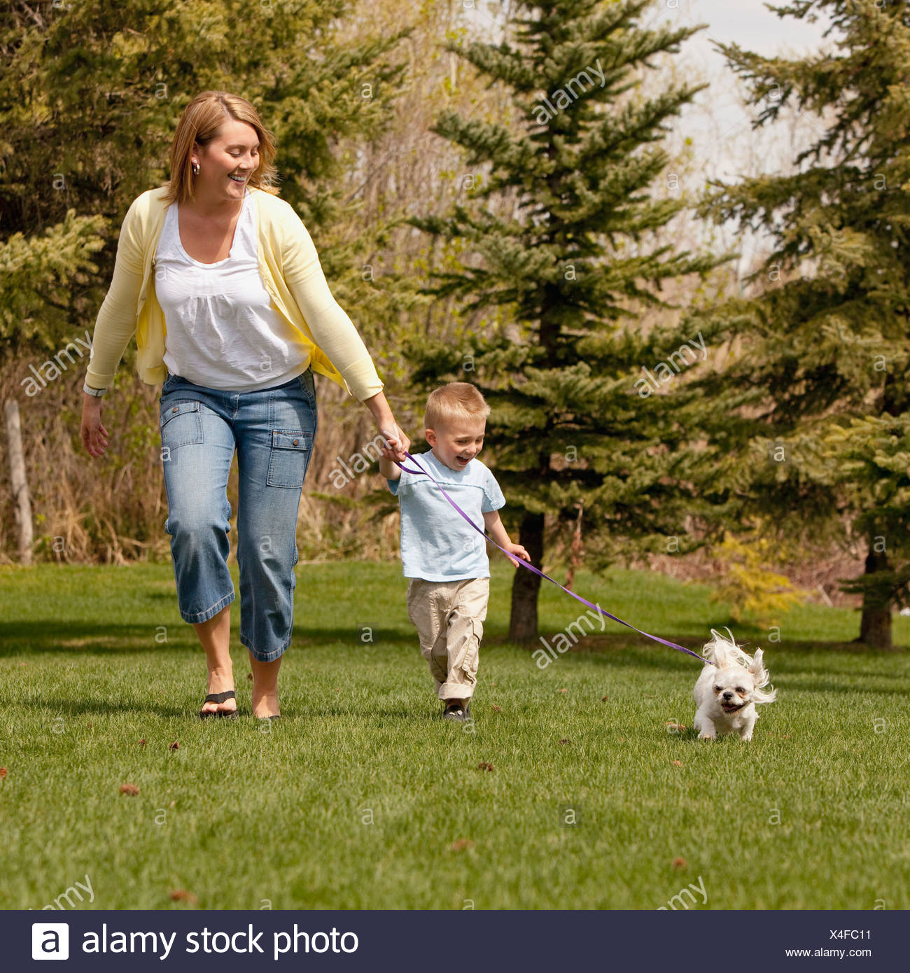 Mother and son running with dog - Stock Image
