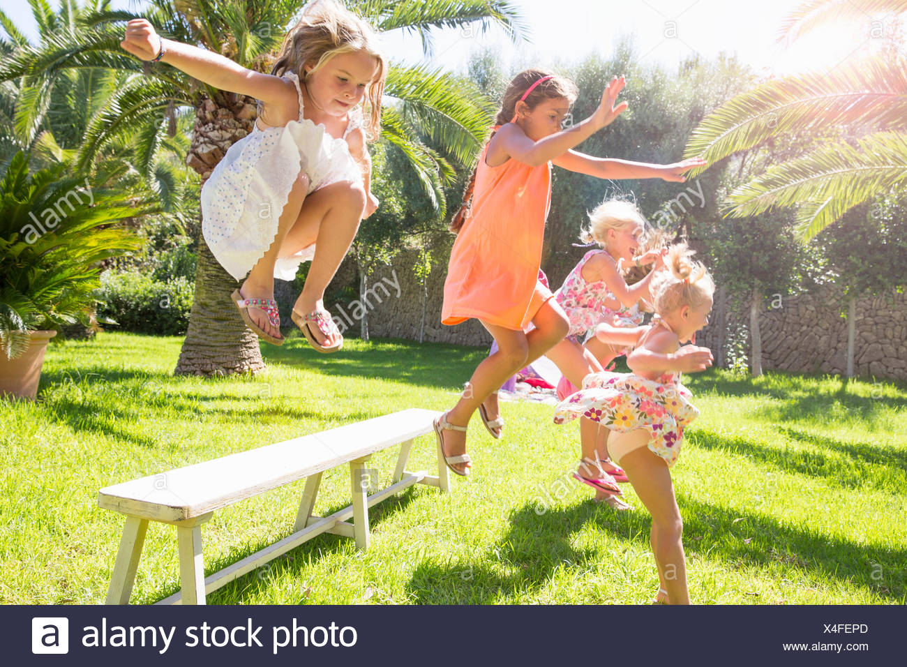 Five energetic girls jumping from garden bench - Stock Image