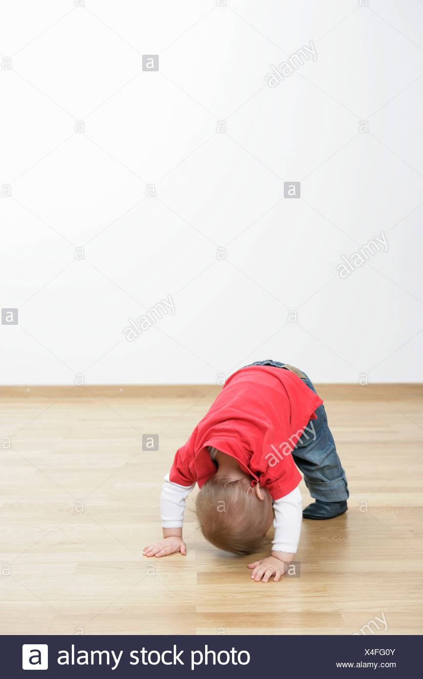 Baby boy trying to stand - Stock Image
