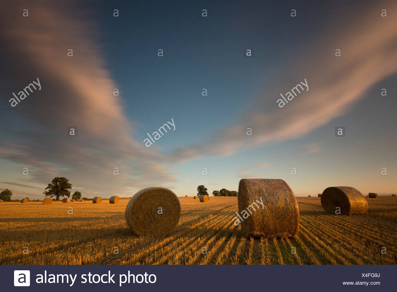 moving clouds on field with straw bales,long exposure Stock Photo