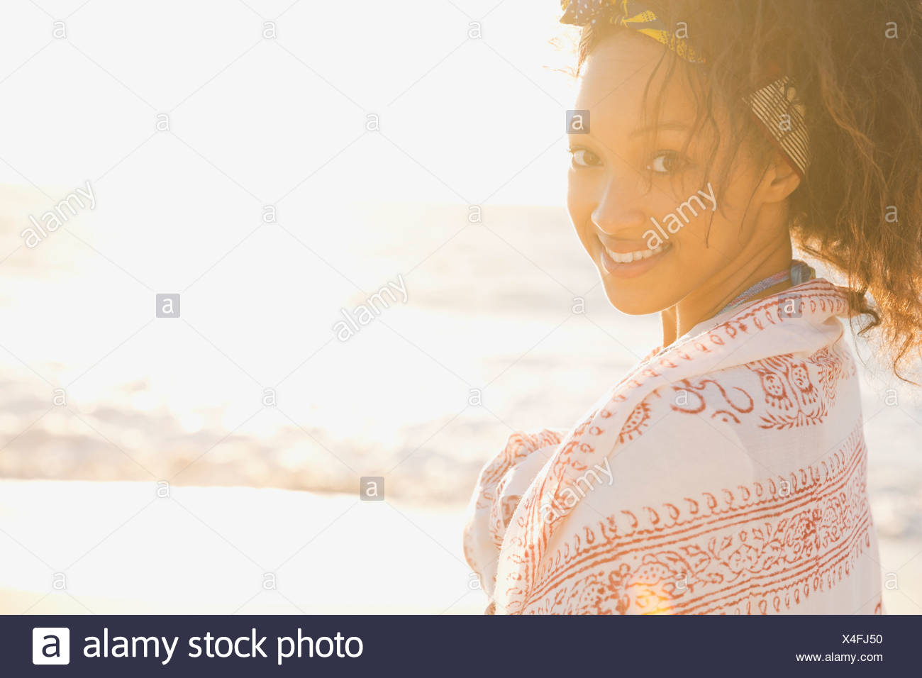 Portrait of woman wrapped in shawl on the beach - Stock Image