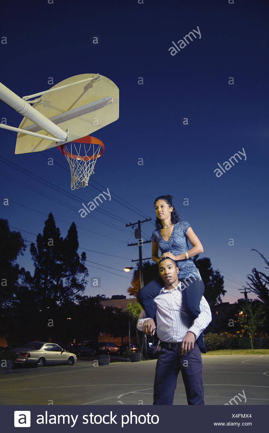 A young man gives a young woman a piggy back ride at a basketball court, Berkeley, California, USA - Stock Image