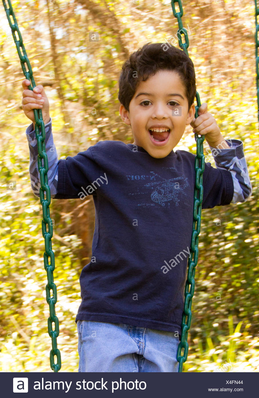 Smiling boy standing on a swing - Stock Image