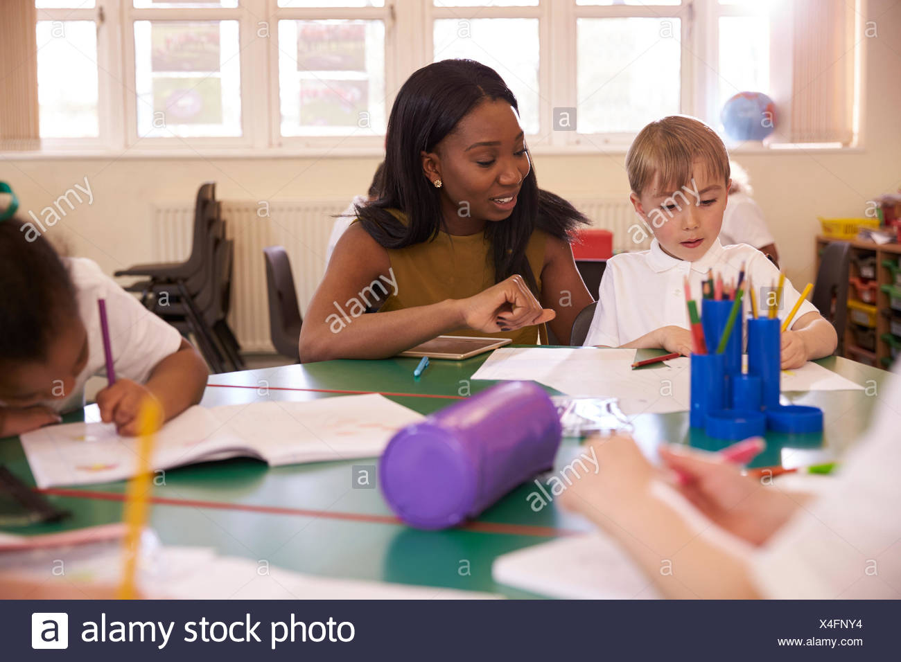 Elementary School Teacher Helping Male Pupil At Desk - Stock Image