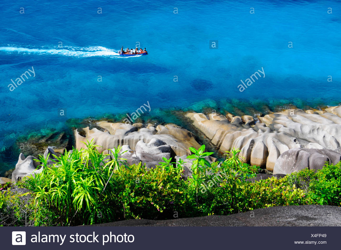 Granite rocks and tropical vegetation in front of a boat on the sea, northwest coast, Mahe, Seychelles - Stock Image