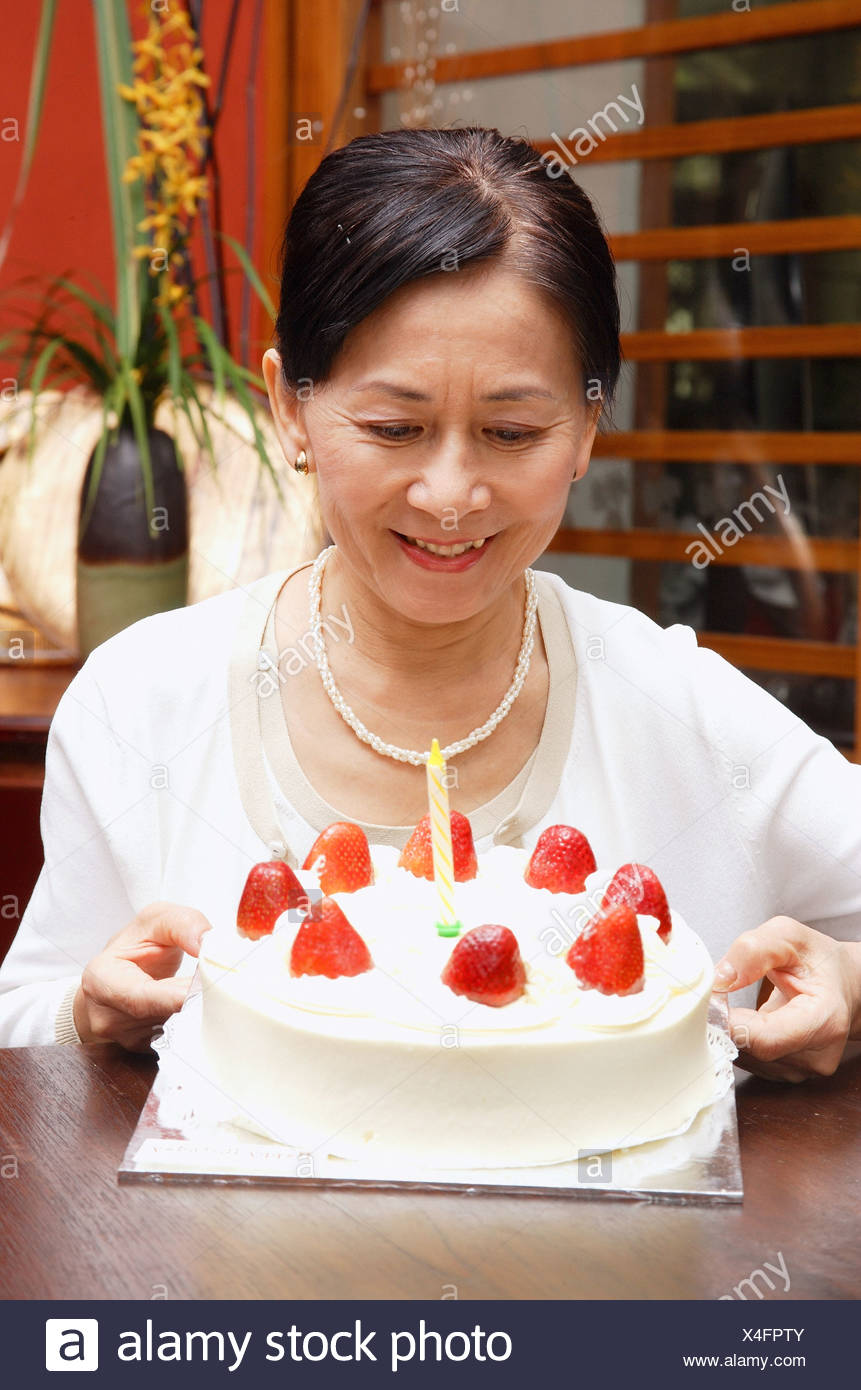 Mature Woman Looking At Birthday Cake Smiling Stock Photo