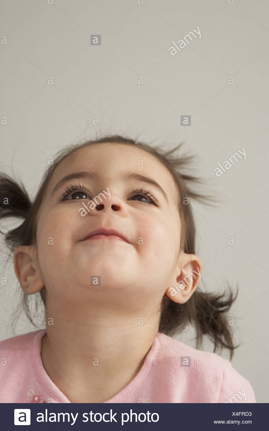 A young girl with brown eyes and dark hair in bunches. Looking upwards with her head thrown back. Stock Photo