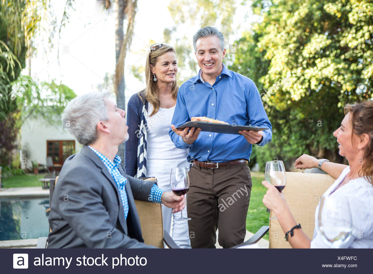 Mature man serving fish cuisine at garden party - Stock Image