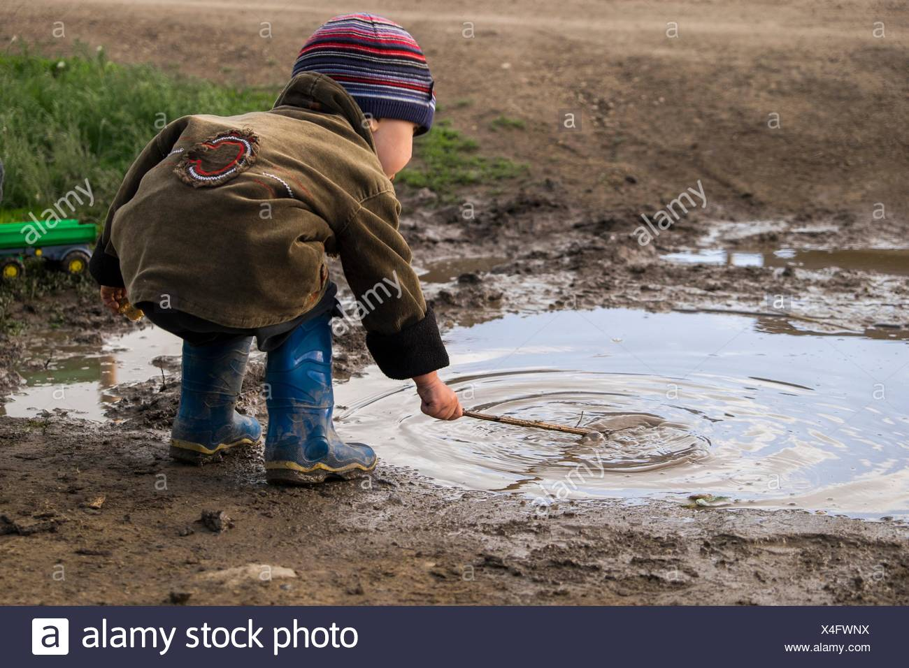Male toddler wearing rubber boots playing with stick in puddle - Stock Image
