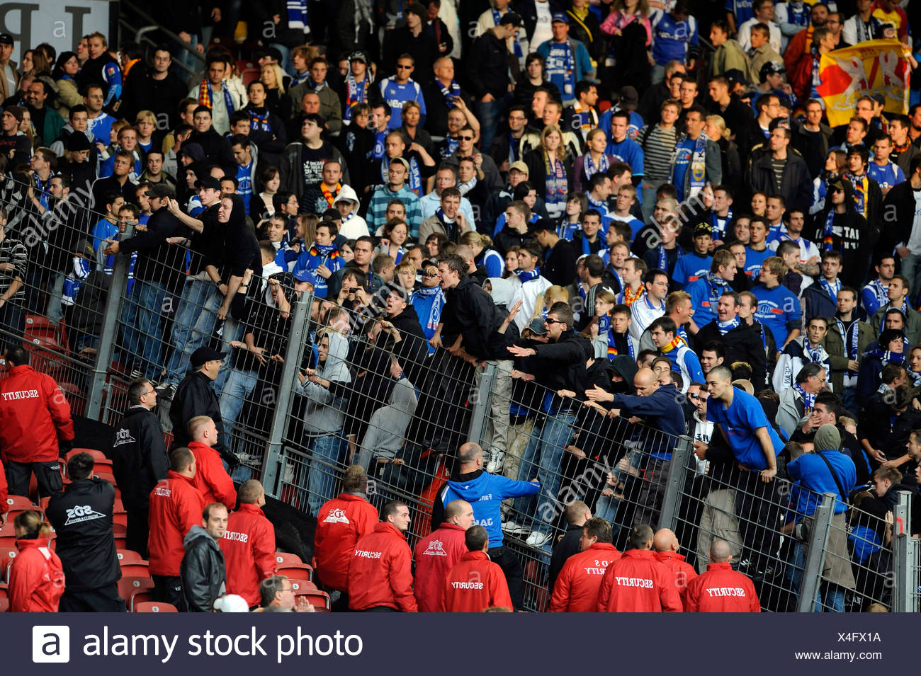Aggressive hooligans climbing a separation fence and threatening security - Stock Image