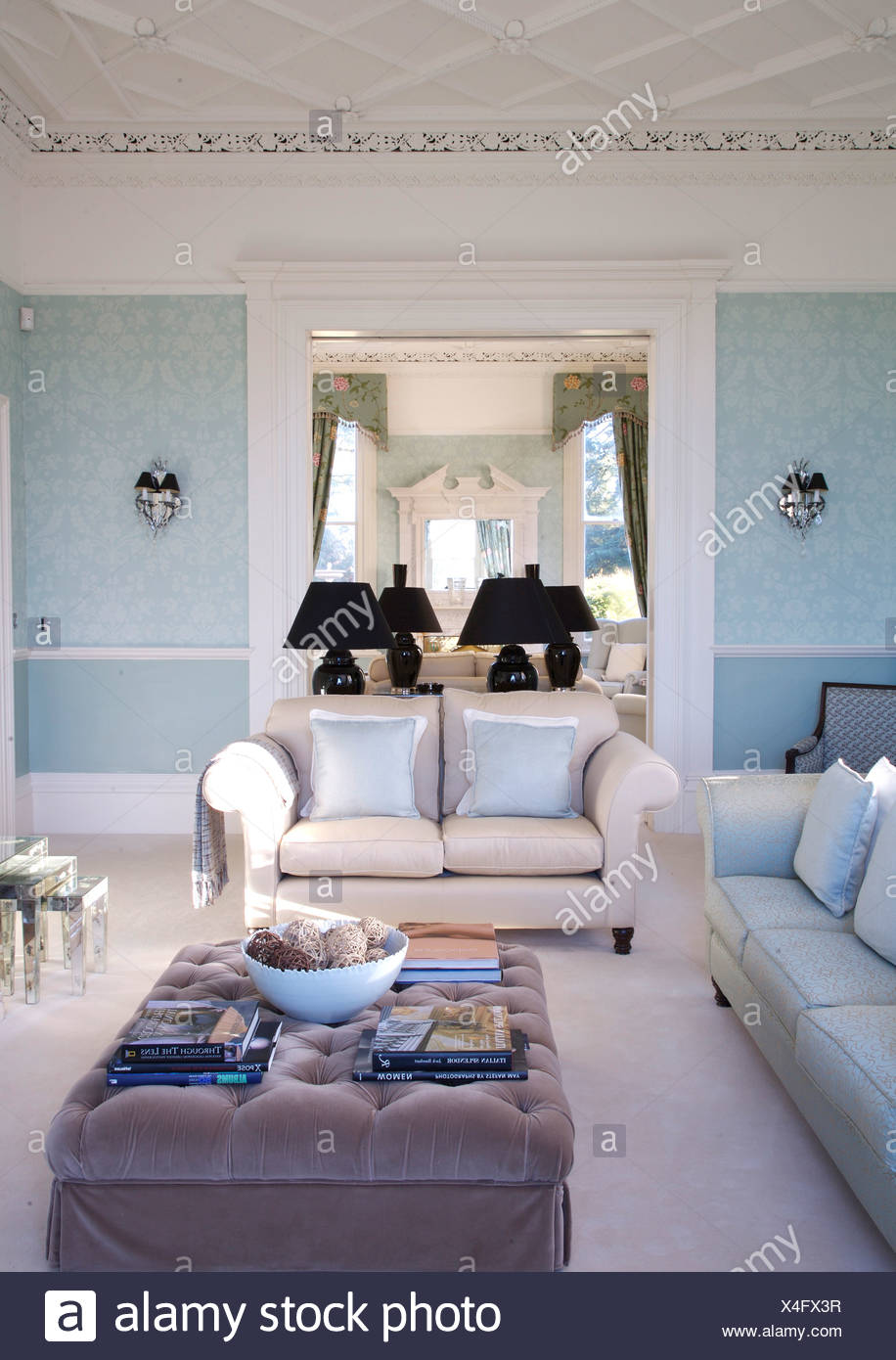 Gray Velvet Ottoman And White Sofas And Carpet In Pale Blue