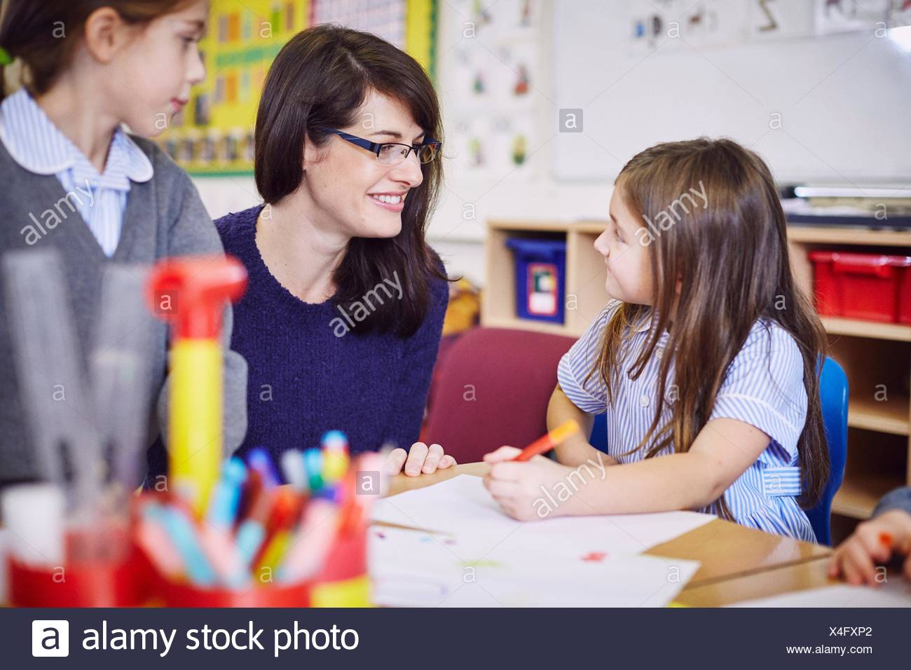 Girls drawing at desks in elementary school classroom - Stock Image