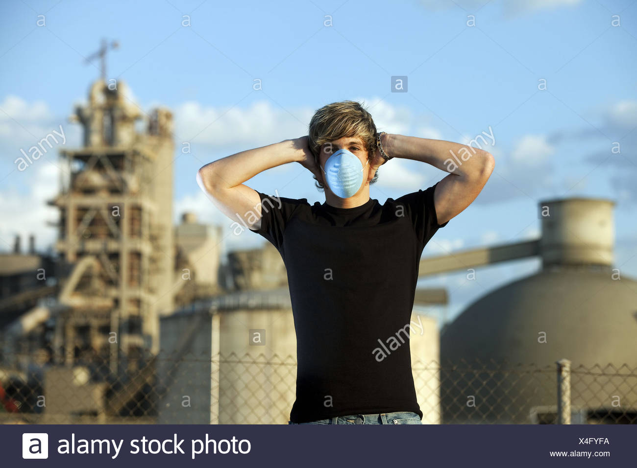 Man with a contamination mask near a cement works - Stock Image