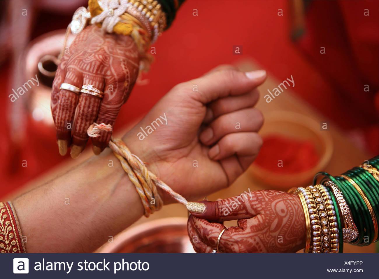 Wedding ritual, Kankana Dhaarana, a turmeric-stained thread wrapped around a turmeric root. - Stock Image
