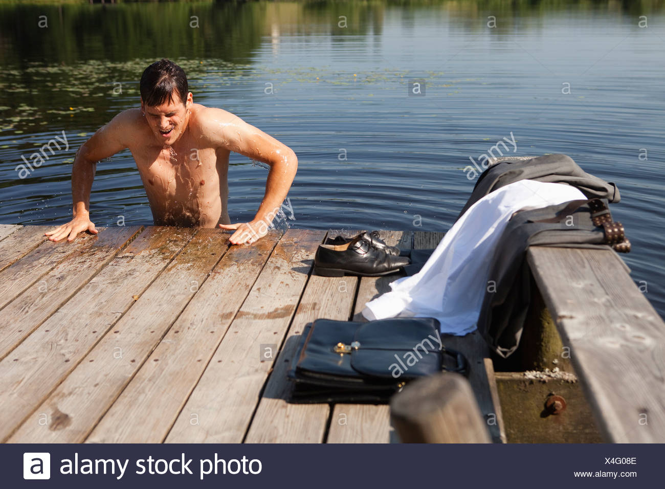 Young businessman coming out of lake water onto pier - Stock Image