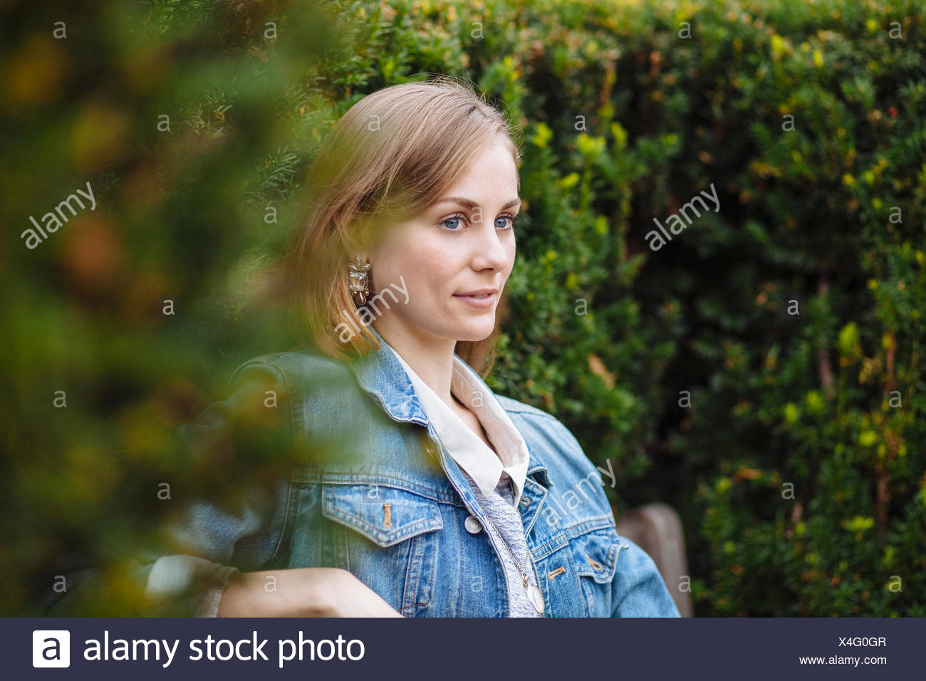 Young woman gazing from park bench - Stock Image