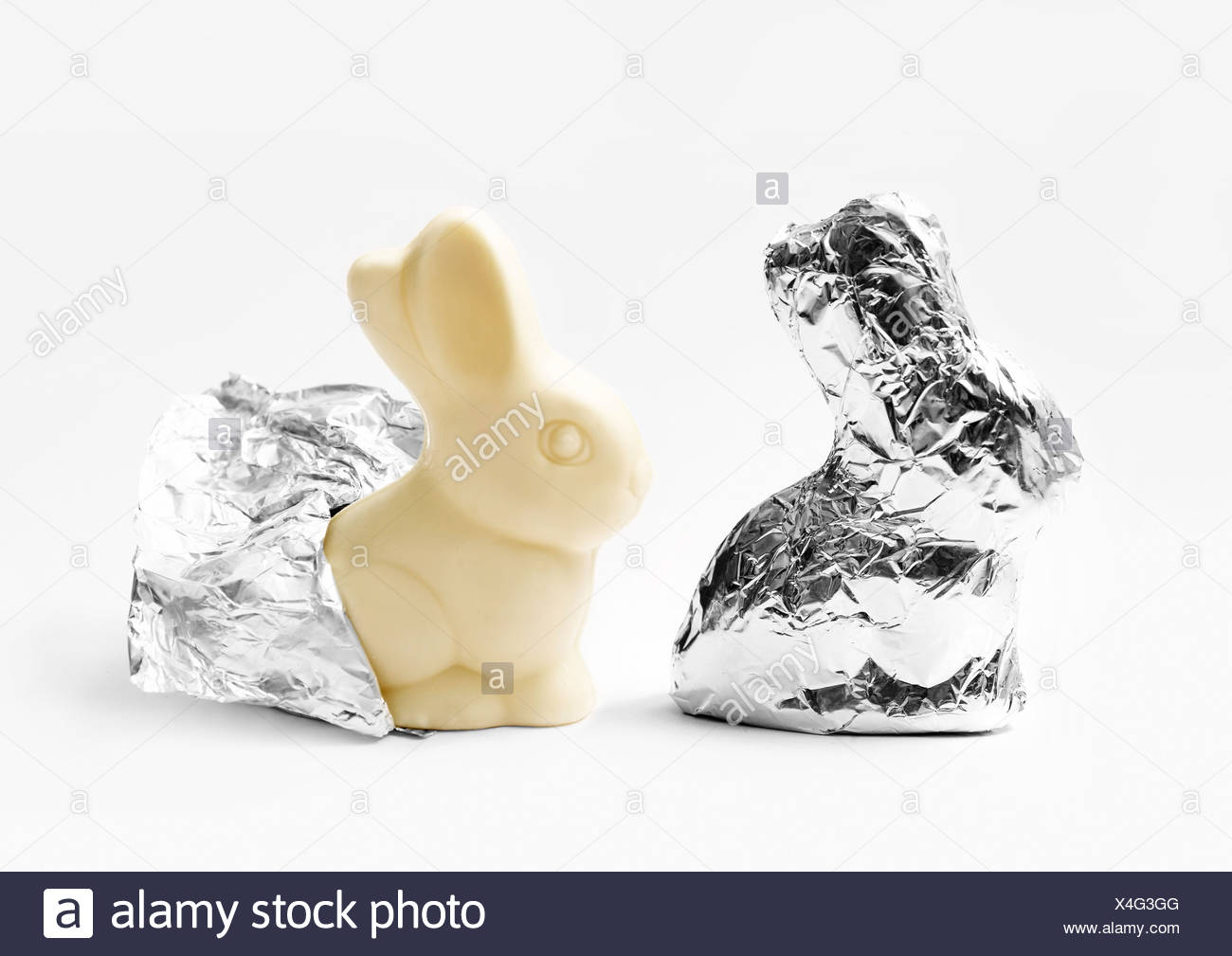 White chocolate rabbits wrapped in aluminium foil - Stock Image