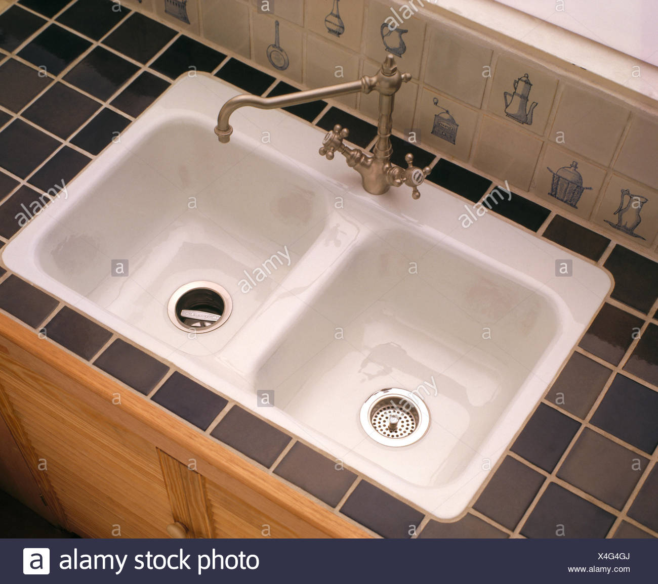 Chrome tap above white porcelain double sinks - Stock Image