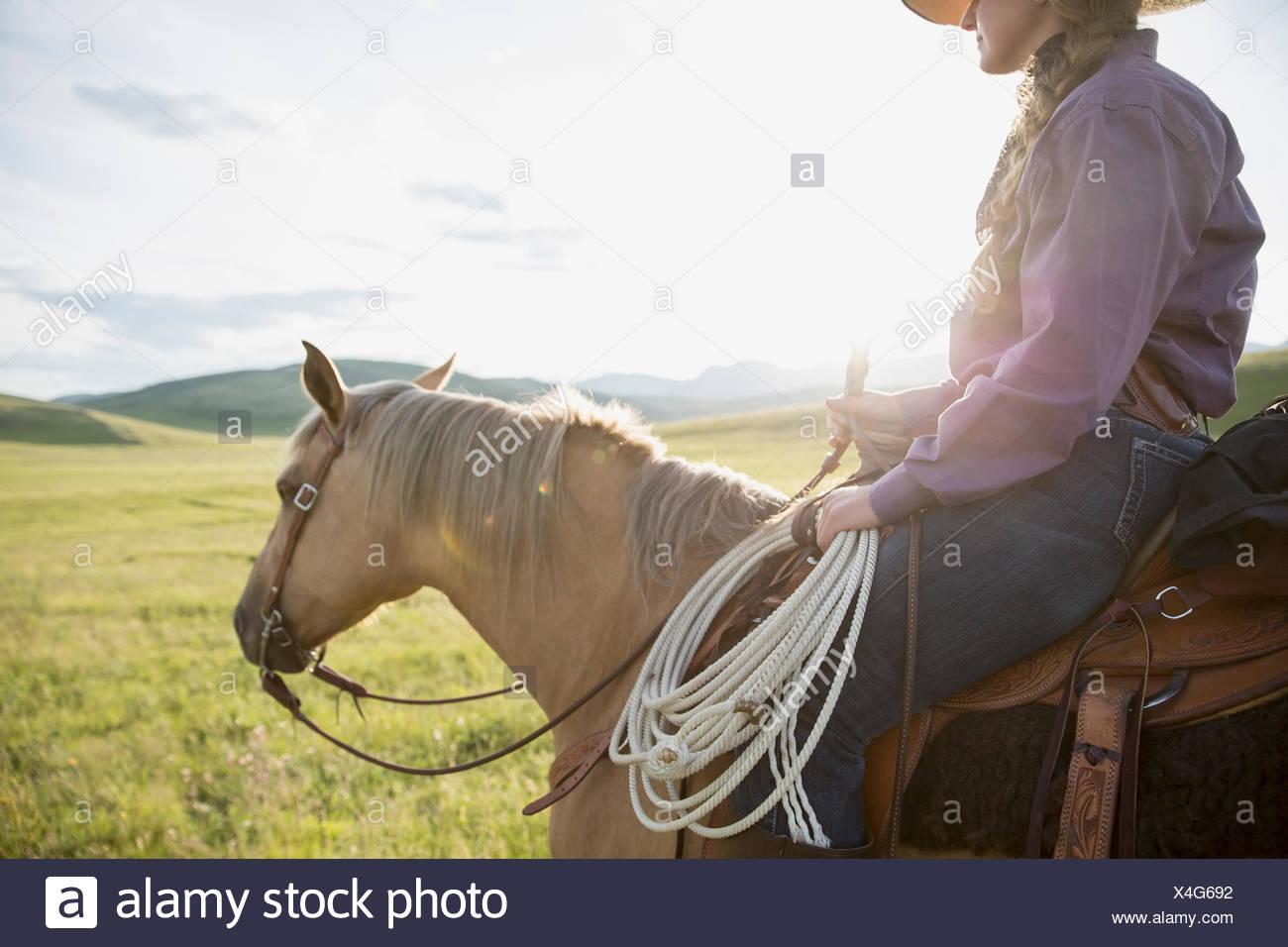 Female rancher horseback riding in sunny remote field - Stock Image