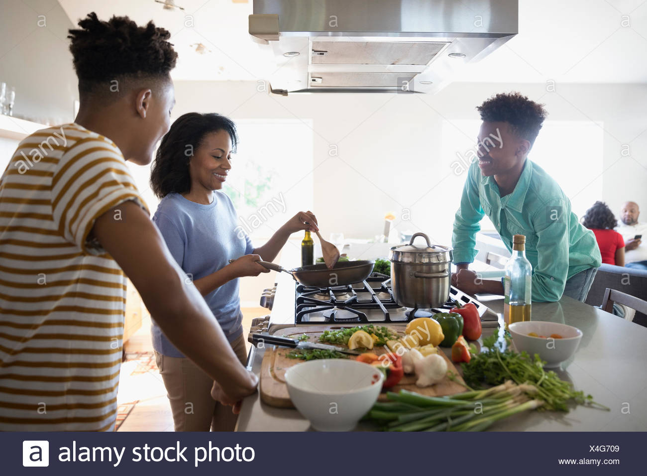 African American mother and teenage sons cooking at stove in kitchen Stock Photo