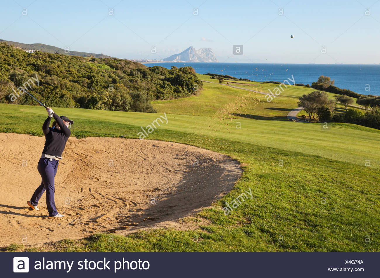 Golfer hitting from bunker at La Alcaidesa Golf Resort with Mediterranean Sea and Rock of Gibraltar, Cádiz, Andalusia, Spain - Stock Image