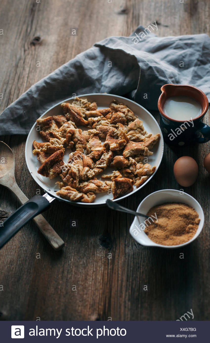 Kaiserschmarrn or shredded pancake in a pan on a rustic wooden table - Stock Image