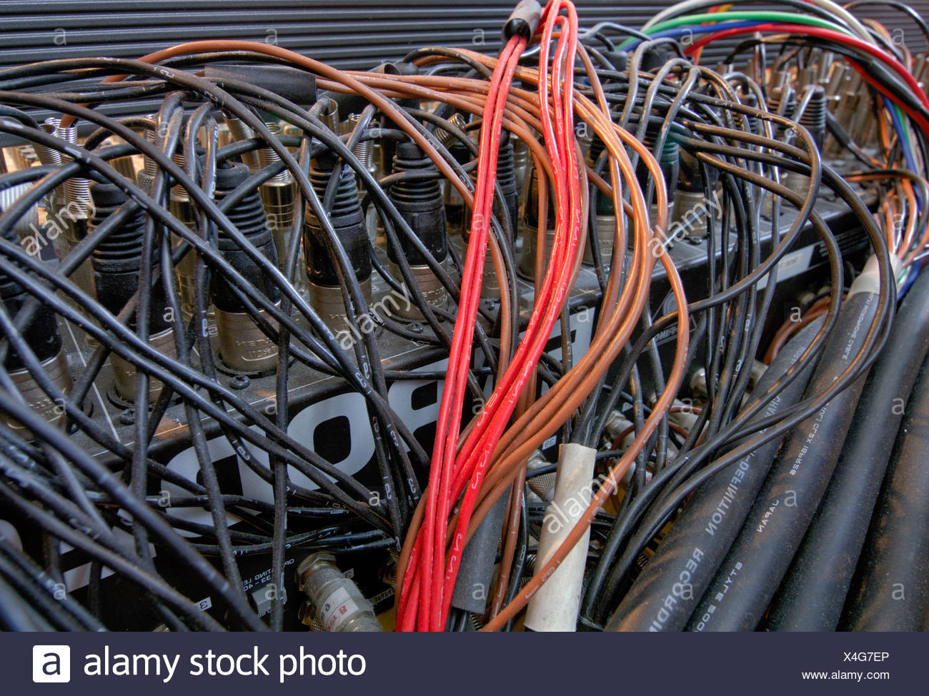 Jumble of cables behind a mixer in a sound studio - Stock Image