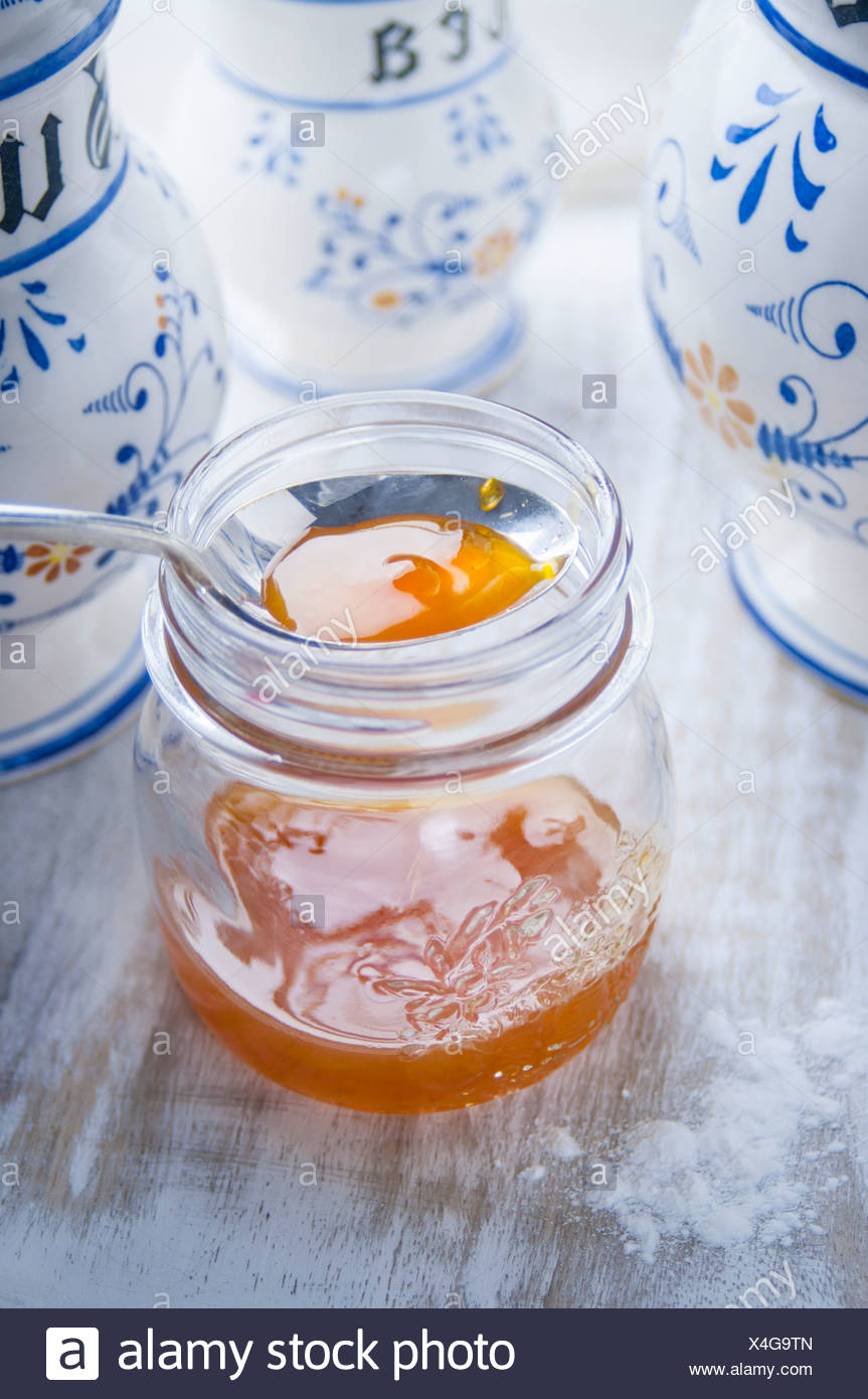 Apricot Jam in a Glass Jar with Kitchen Canisters - Stock Image
