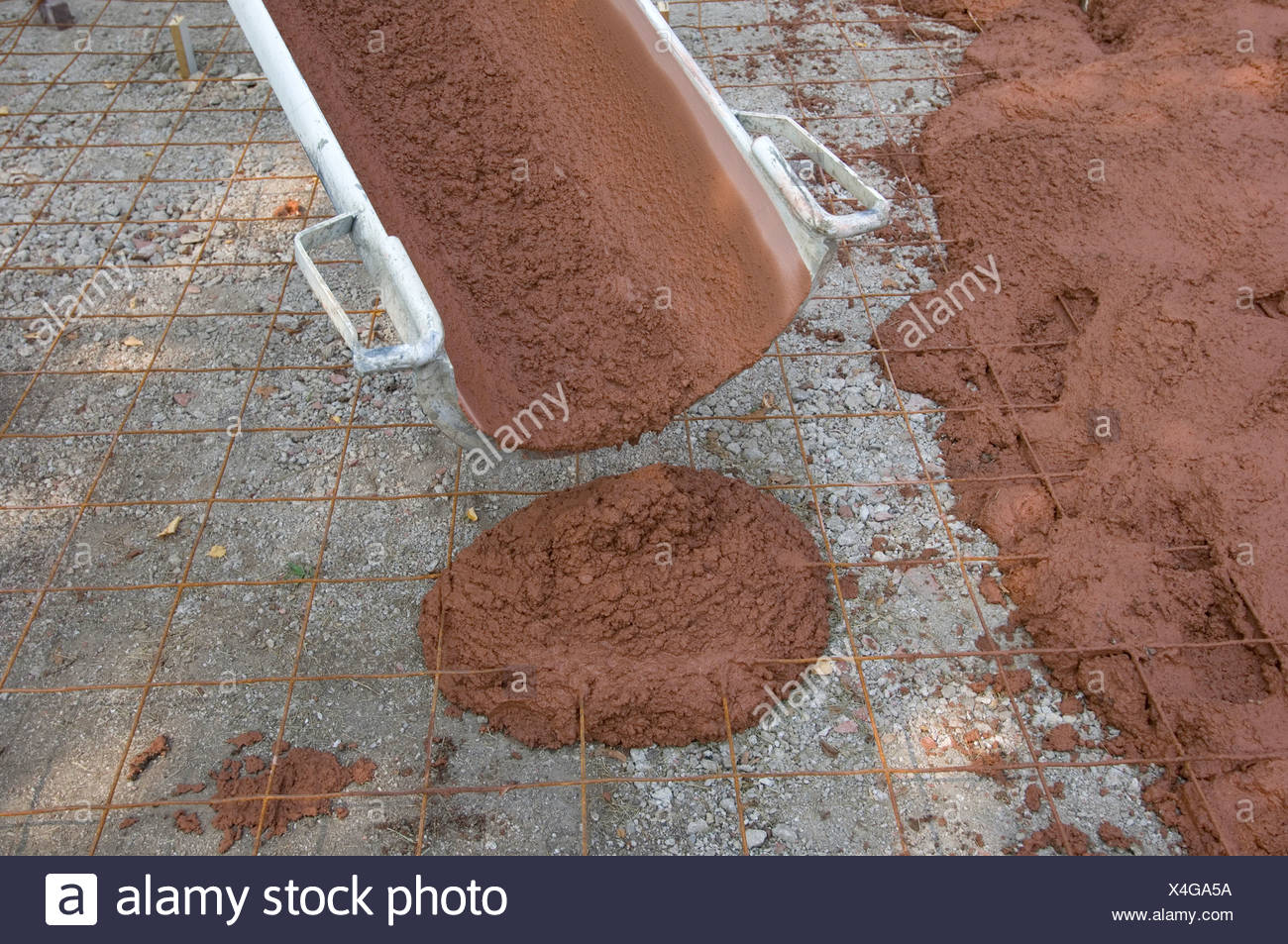 Red-tinted concrete is poured as a new driveway. - Stock Image