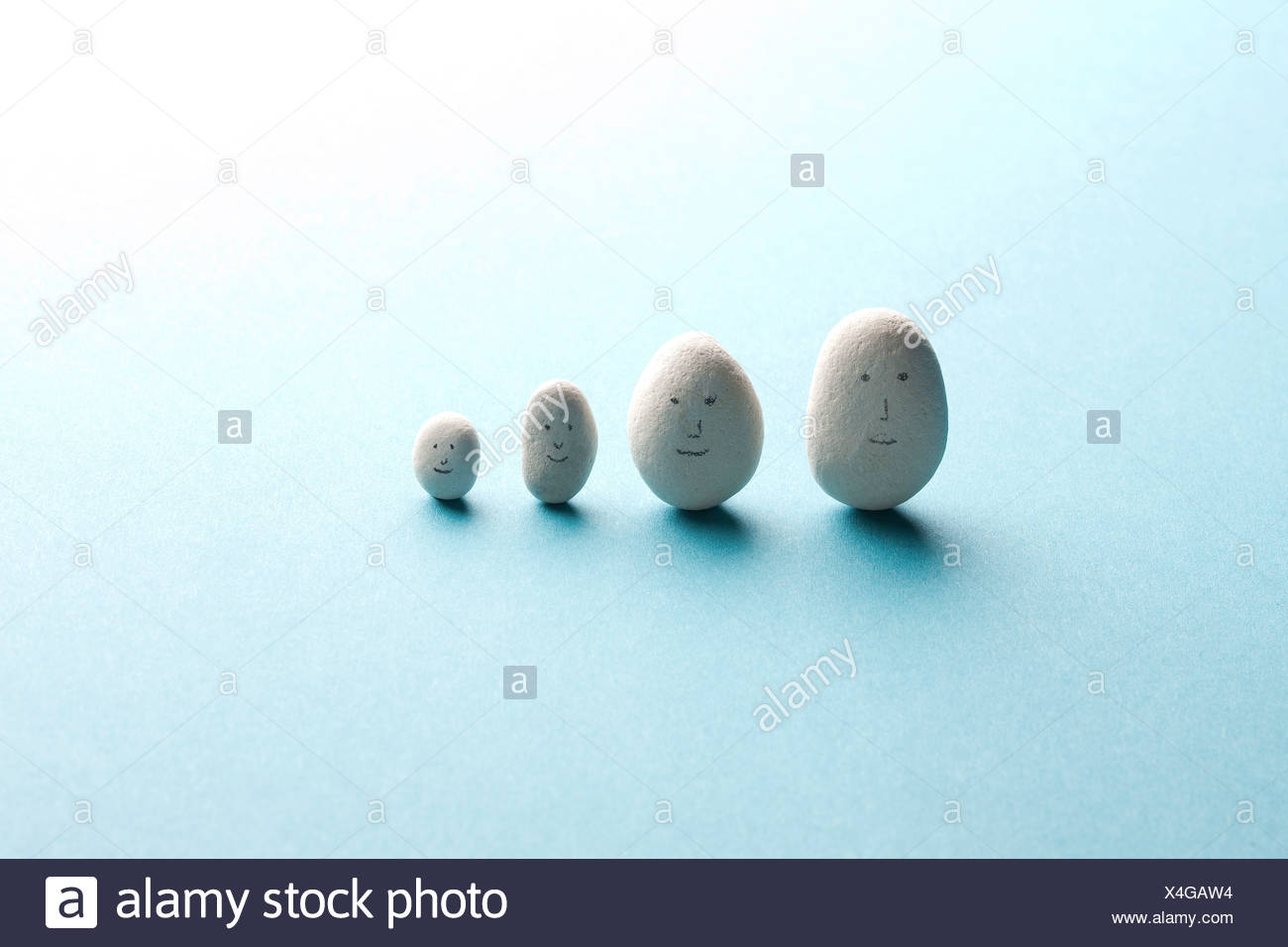 White stones with faces drawn on them - Stock Image
