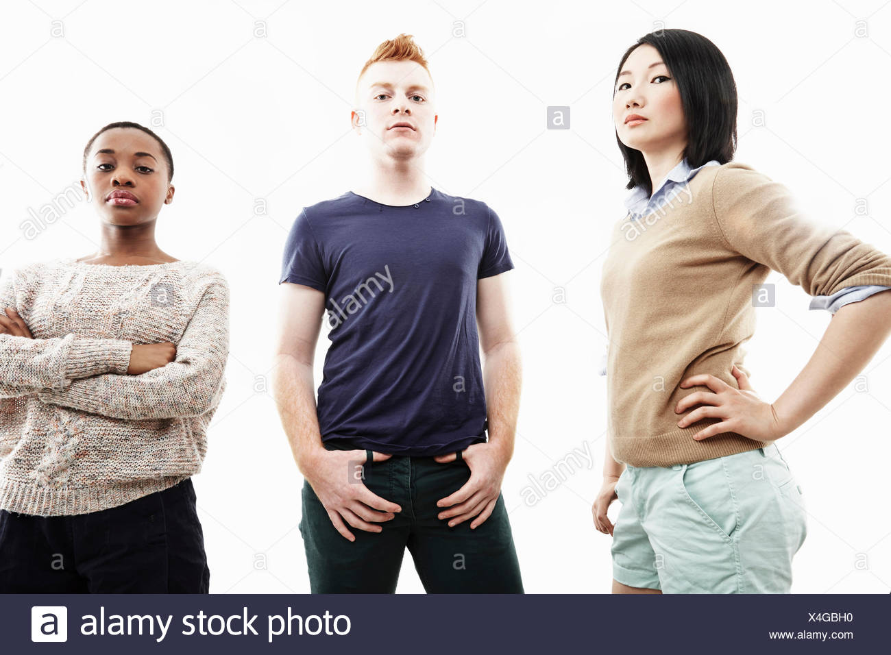Studio portrait of three young individual adults - Stock Image
