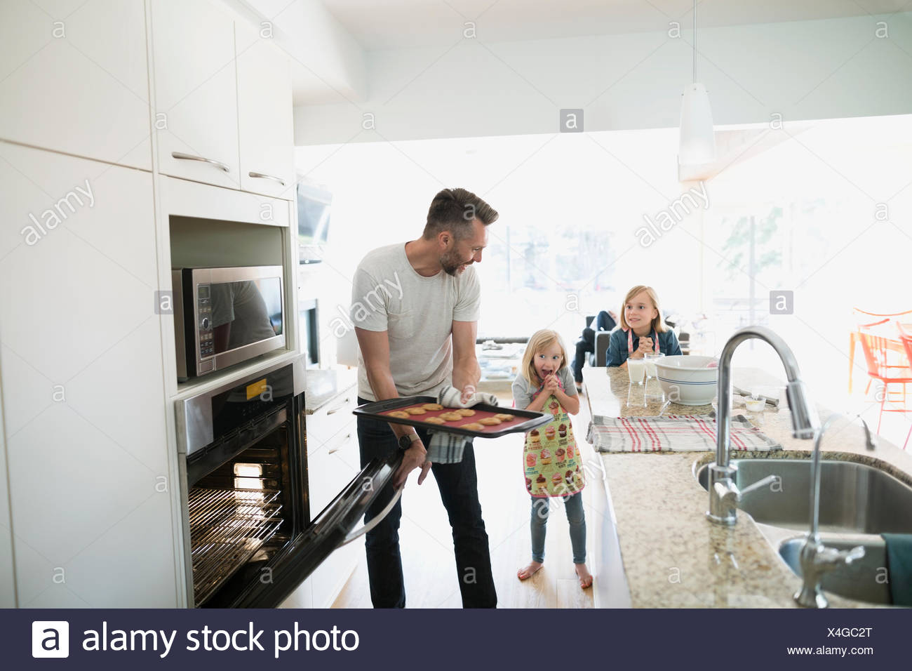 Father and daughters baking in kitchen - Stock Image
