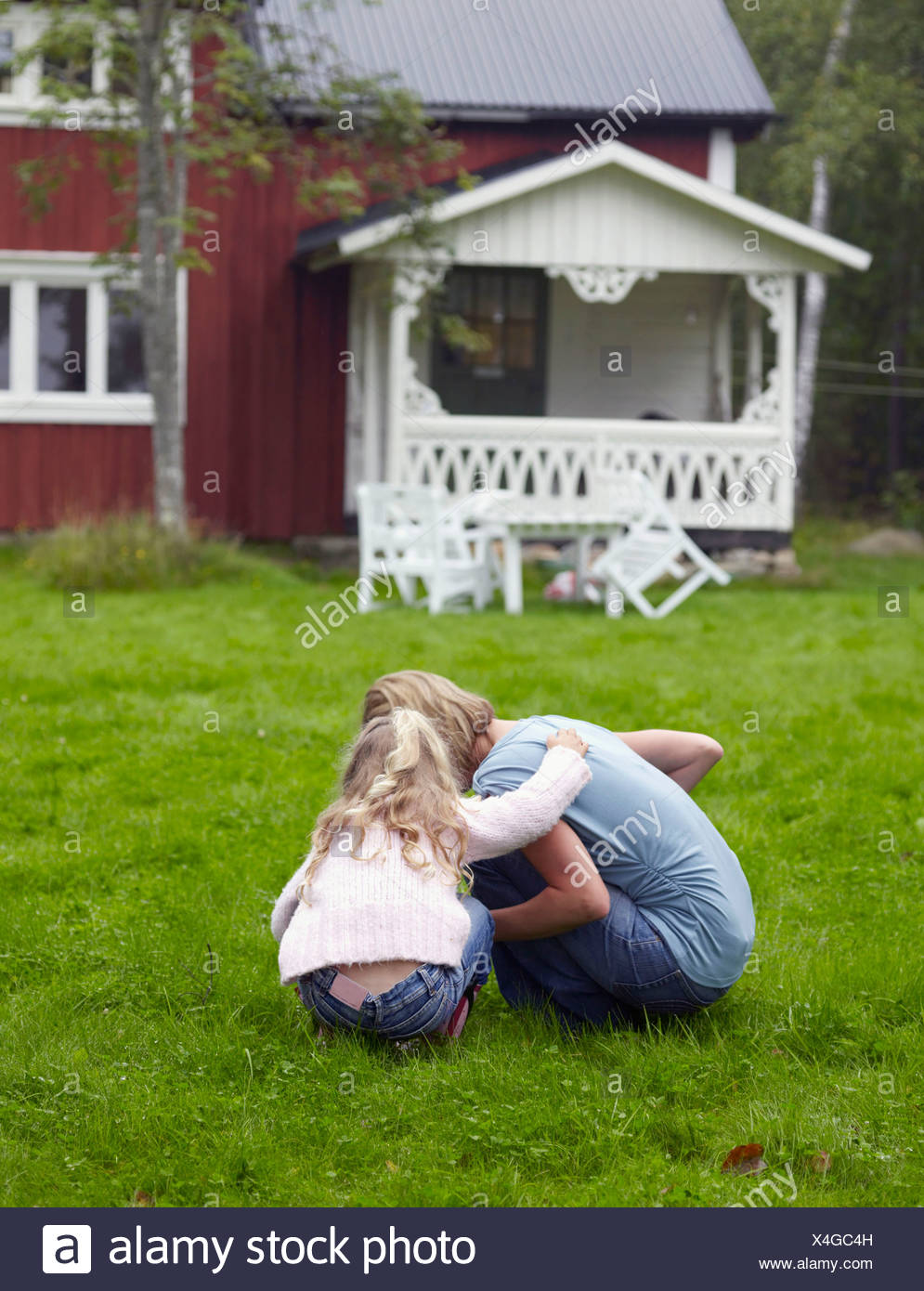 Woman with young girl crouched down in yard. - Stock Image