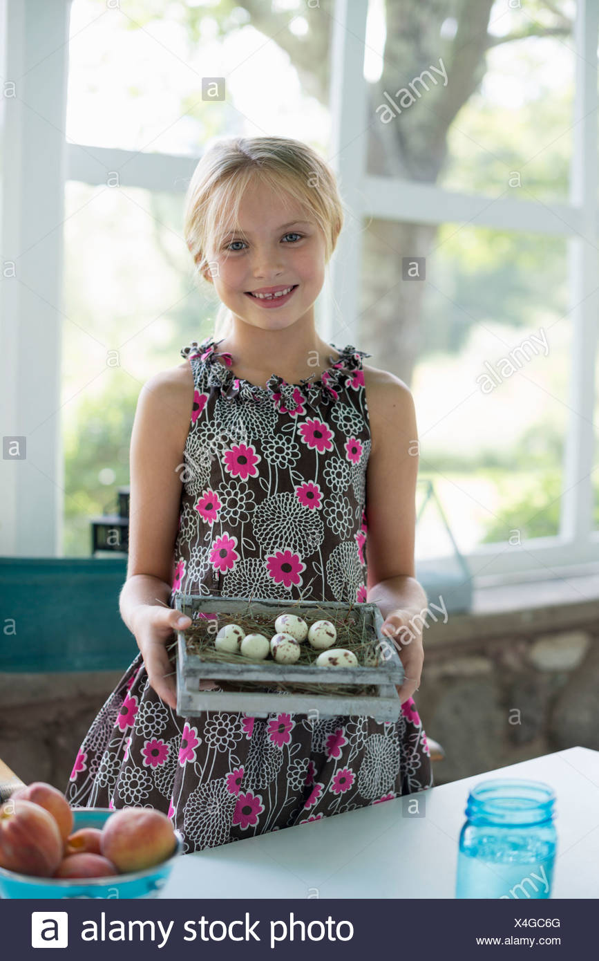 A young girl in a floral dress, examining a clutch of speckled bird eggs in a box. - Stock Image