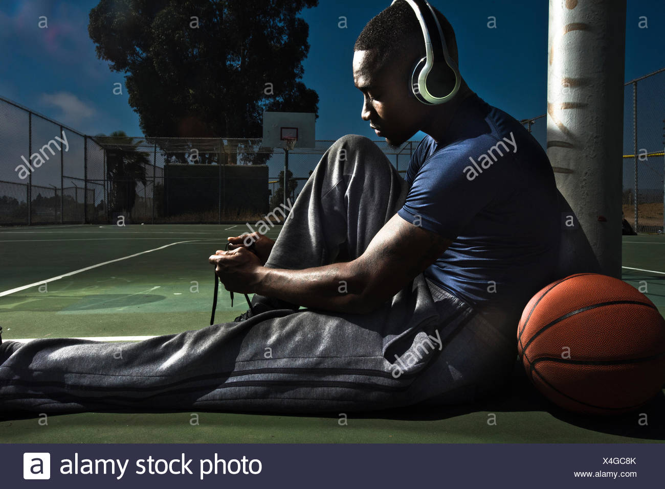 A basketball player laces up his shoes. - Stock Image