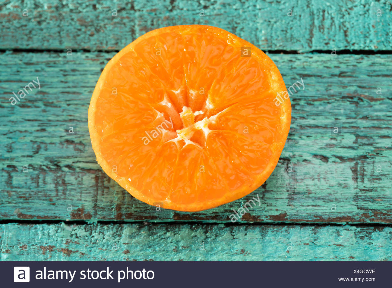 Close-up view of fresh orange slice on blue wooden table - Stock Image