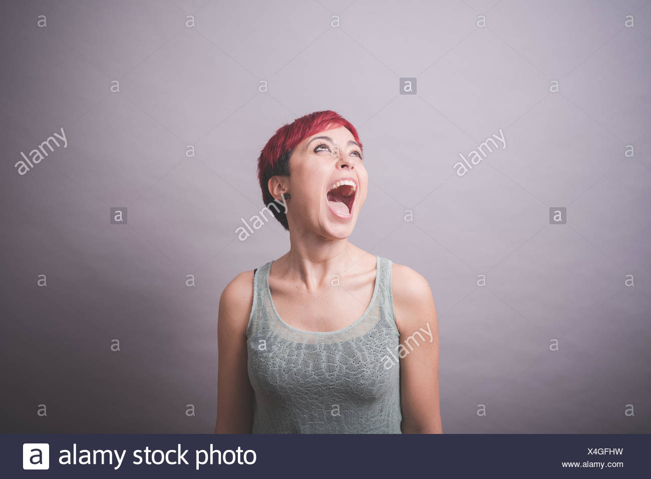 Studio portrait of young woman with short pink hair shouting - Stock Image
