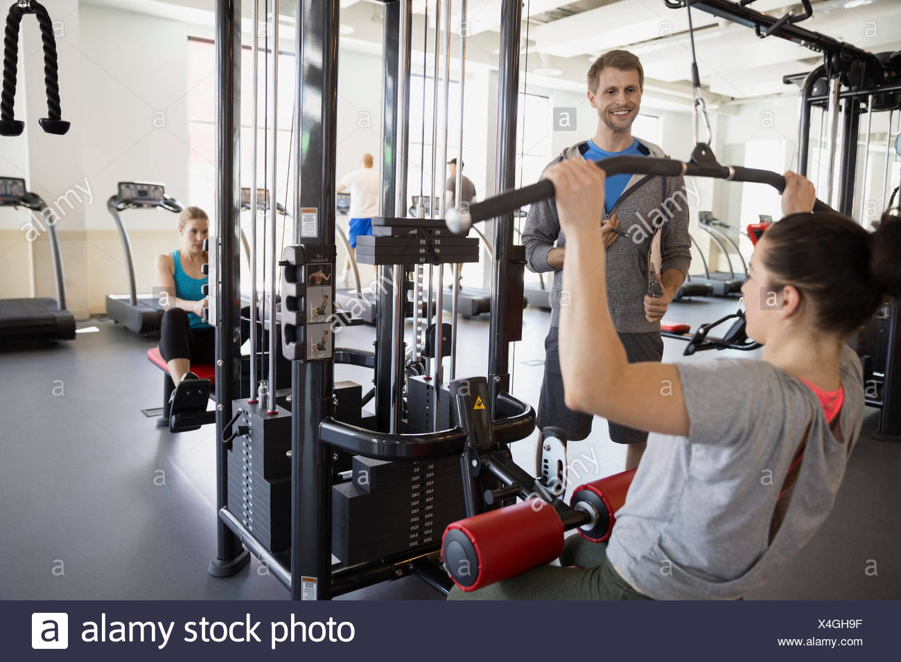 Woman doing lat pulldown exercise at gym - Stock Image
