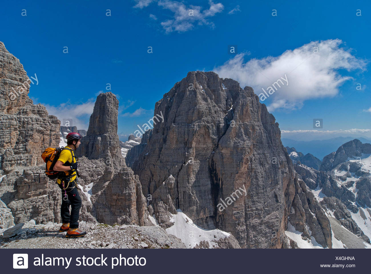 Brenta, Trentino, Italy. Climber on the via ferrata 'Sentiero delle Bocchette Centrali'. In the background the Cima Brenta Alta and the famous Campanile Basso - Stock Image