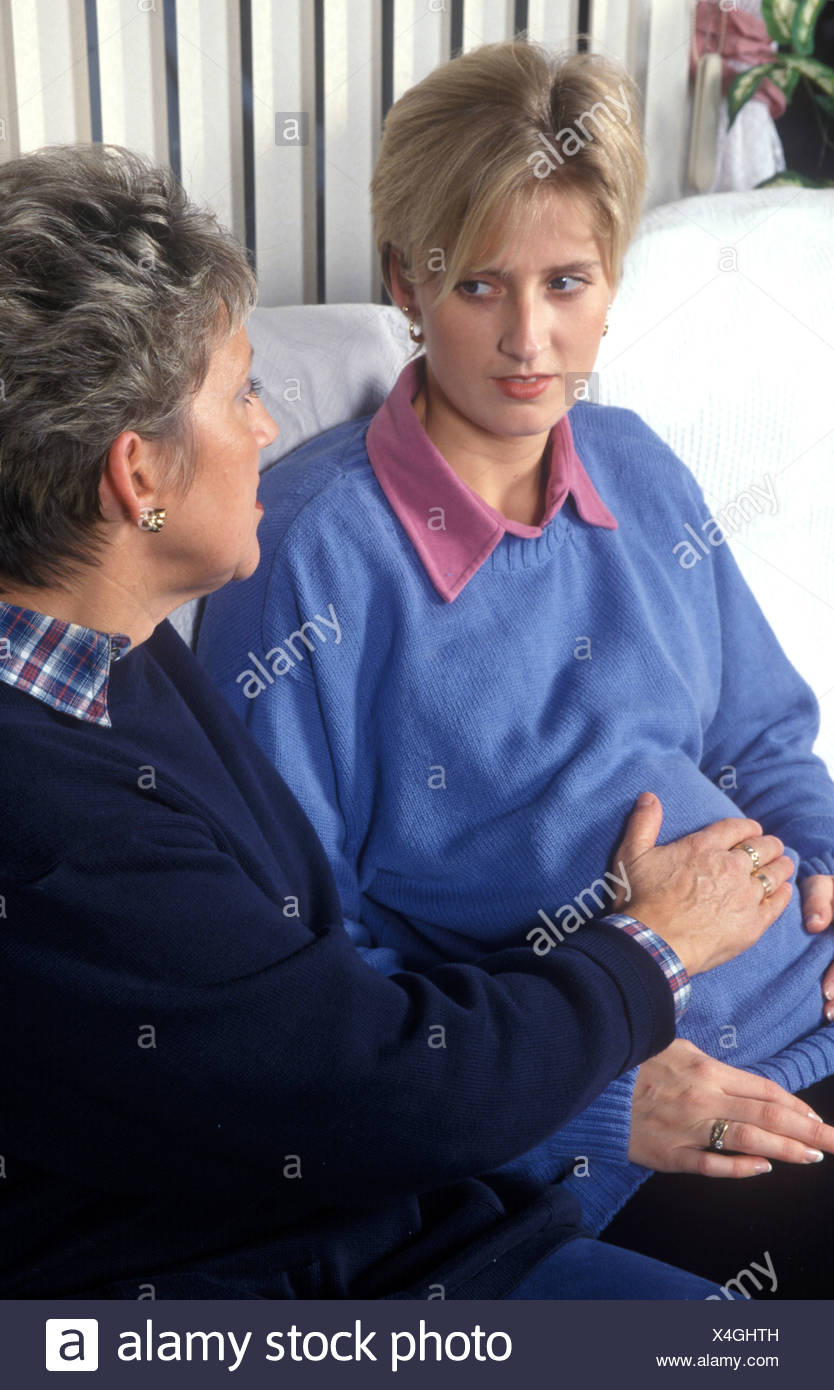 pregnant woman sitting on a settee with a friend or mother talking or touching her tummy - Stock Image