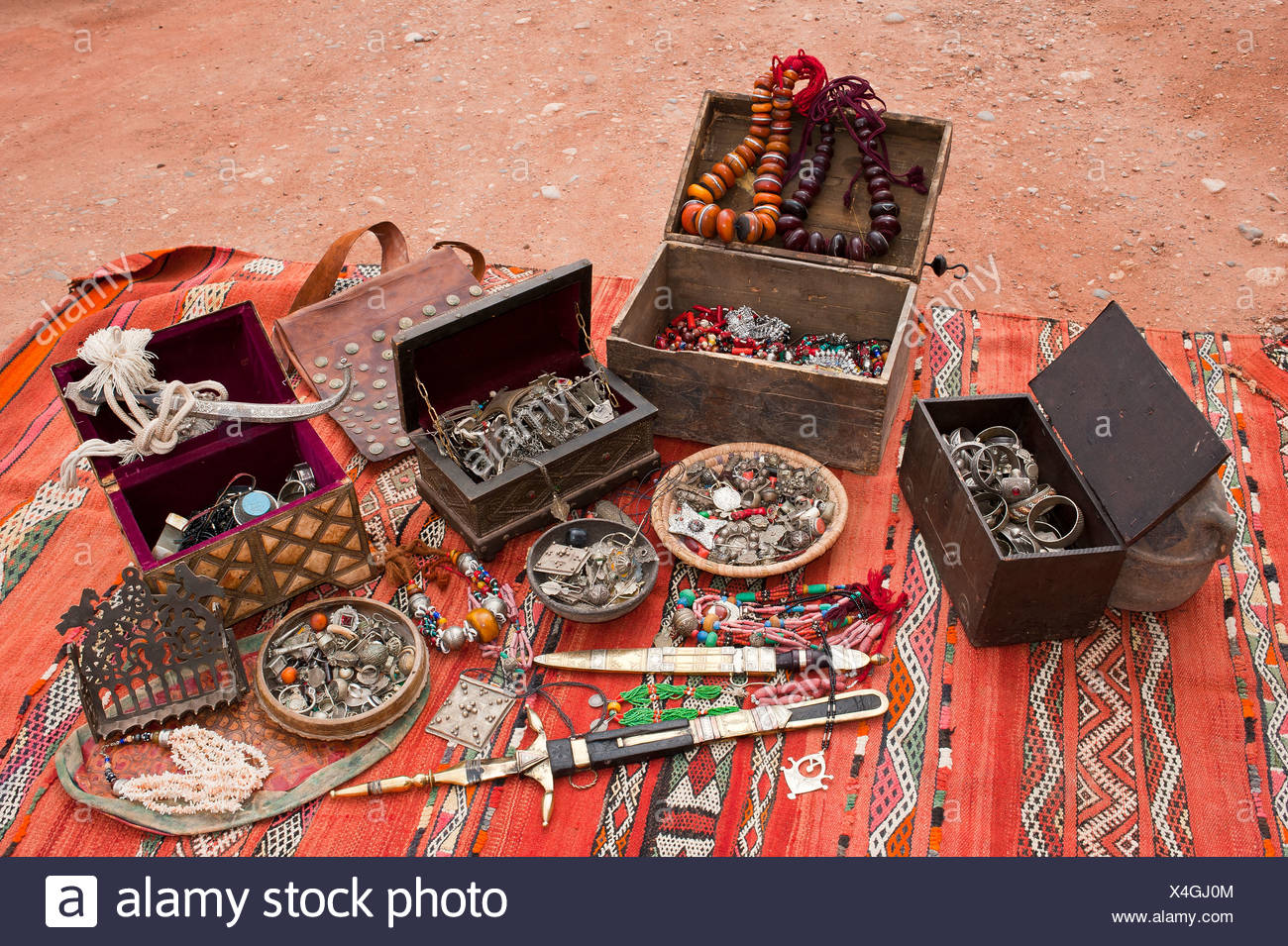 Little treasure chests, traditional oriental jewellery and decorated Touareg knife spread on a carpet, Morocco, Africa - Stock Image