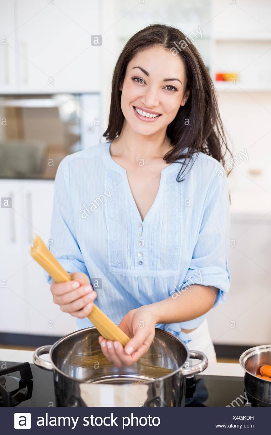 Woman preparing spaghetti noodles in kitchen - Stock Image