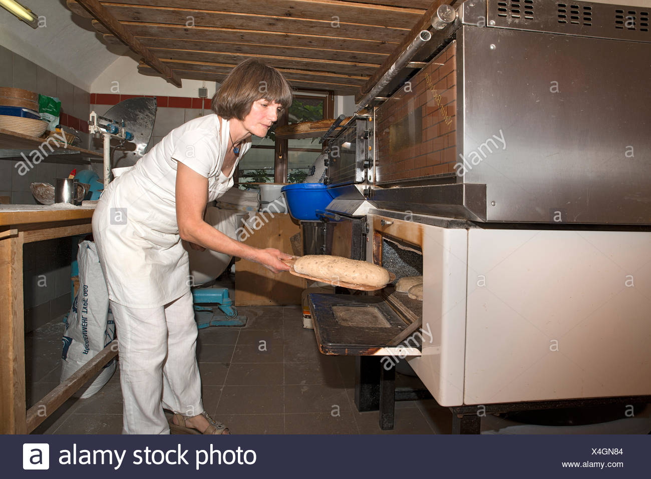 Farmer making bread in her own bakery at the farm, feeding the oven, Tyrol, Austria - Stock Image