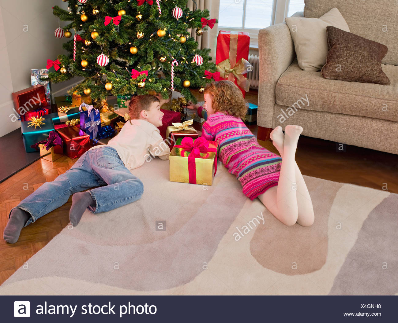 Boy and girl looking at gifts under Christmas tree - Stock Image