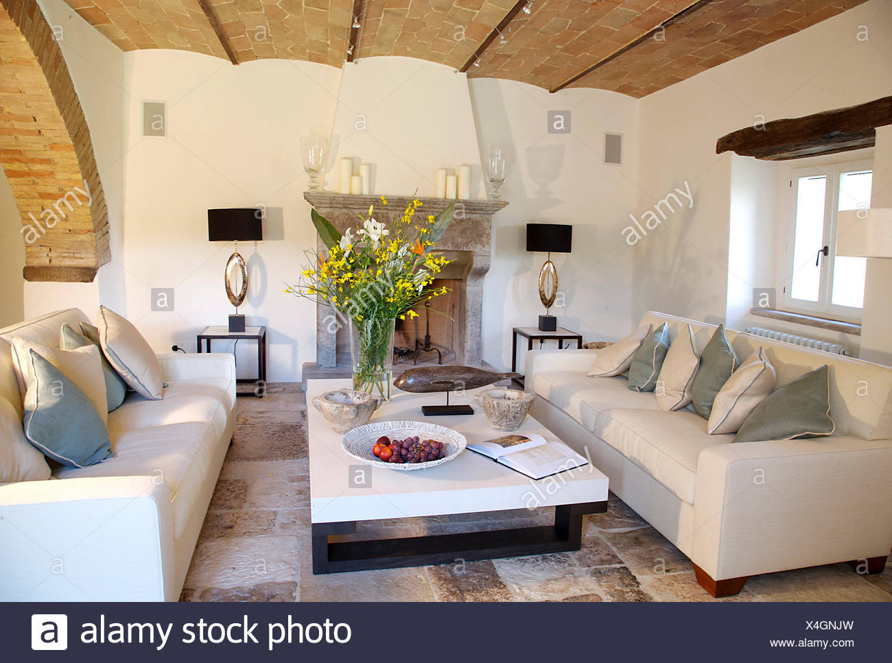 Modern white sofas and coffee table with arrangement of ...