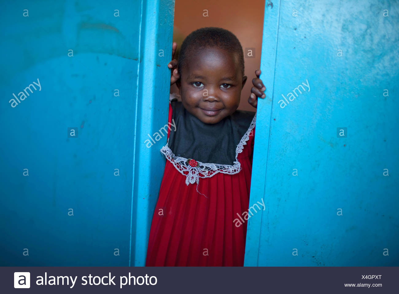 little girl in a red cloth looking out of a blue door, Burundi, Bujumbura Mairie, Bujumbura - Stock Image