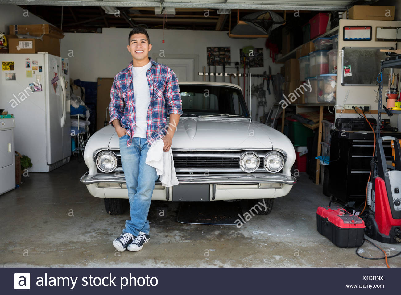 Portrait smiling young man with vintage car garage - Stock Image