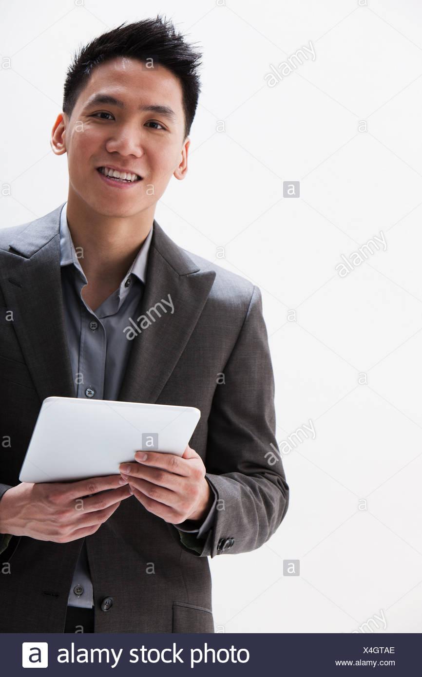 Young Asian businessman holding digital tablet, studio shot - Stock Image
