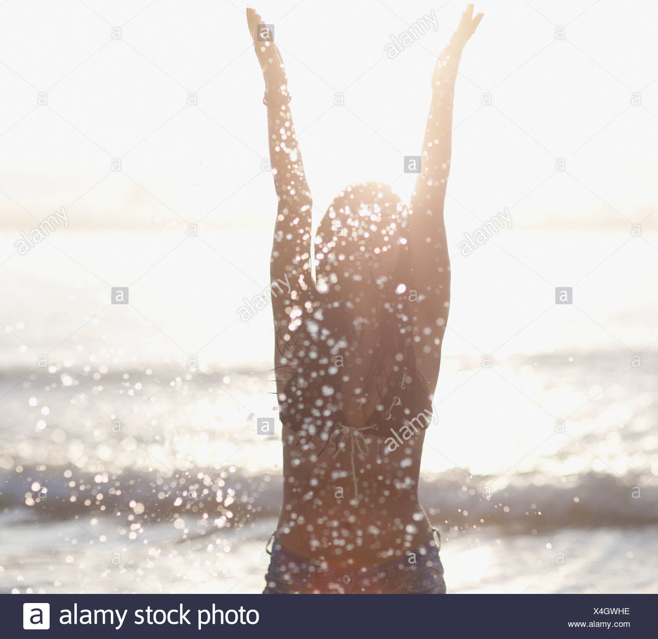 Woman playing in waves at beach - Stock Image